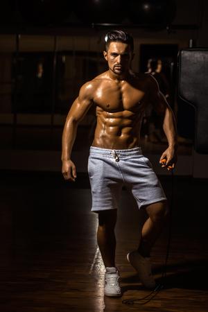 saltar la cuerda: apuesto joven con sexy cuerpo mojado torso desnudo muscular y la celebraci�n de saltar la cuerda en el pecho