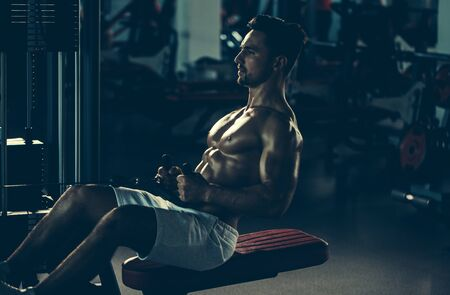bare chest: Handsome young man with sexy muscular wet body and bare chest training with heavy exercise equipment in gym