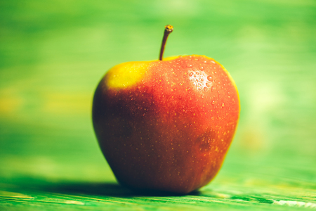 vitamine: fresh red apple with water drops on bright textured green blurred wooden background