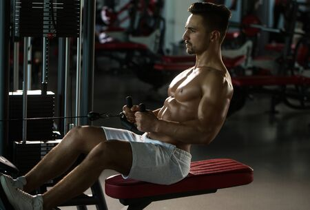 nackte brust: Handsome young man with sexy muscular wet body and bare chest training with heavy exercise equipment in gym