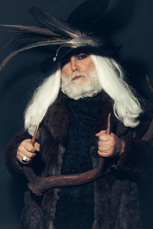 hair feathers: Druid old man with long grey hair beard in hunter hat with bird feathers and fur coat with deer antlers in hands on dark background Stock Photo