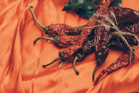 bay leaf: dried red wrinkled chilli pepper or capsicum in rope with green bay leaf on orange textured fabric background, copy space