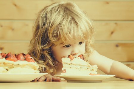 strawberry blonde: cute little boy child with long blonde hair eating tasty creamy pie or cake with red strawberry fruit
