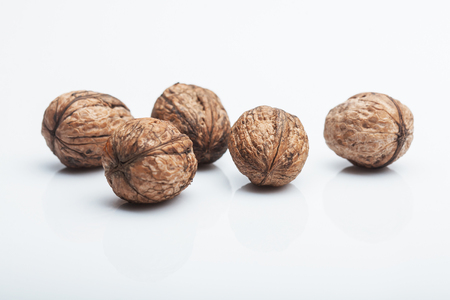 nutshells: hard mature walnuts in shell brown color isolated on white background, copy space
