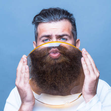 expressive face: young emotional bearded man with expressive face behind big round magnifying glass in hands as smiley on grey background