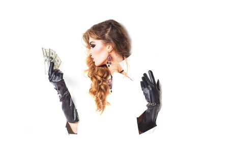 long gloves: Pretty woman with long lush curly hair holding money in hands with black leather gloves in torn paper isolated on white background