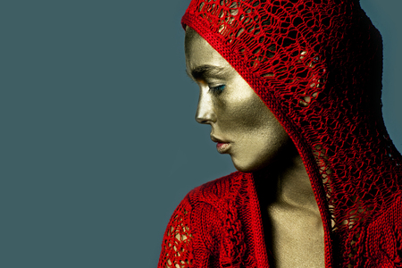knitted jacket: Young woman with golden painted face in red knitted jacket with hood on grey background, closeup copy space