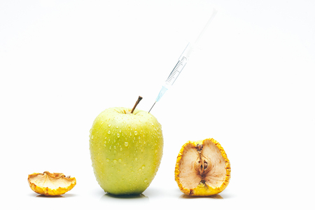 Ripe fresh apple fruit with water drops and wrinkled peel getting rejuvenation procedure by syringe needle isolated on white background. Aging concept. Botox injection concept Imagens
