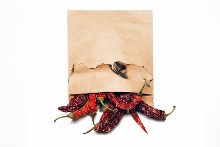 scorched: brown scorched paper envelope with dried red wrinkled chilli pepper inside isolated on white background, copy space Stock Photo