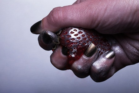 vitamine: female hand crumple strawberry covered with silver paint with seed texture on grey background closeup