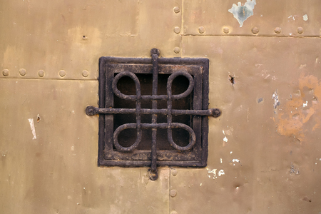 grating: Small square medieval metal wrought grating window on old armor iron background closeup Stock Photo