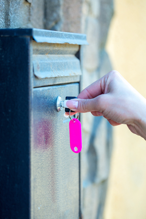 opens: Female hand opens metal post box for correspondance with key on mural background
