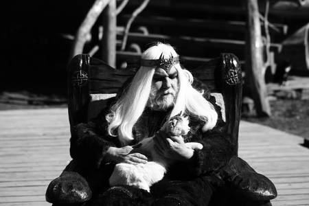 druid: Druid old man with long grey hair beard with crown in fur coat holds cat and sits in wooden chair black and white on log house background