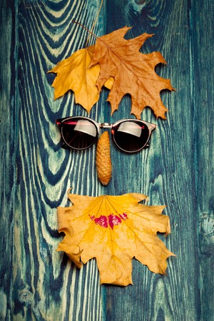 pinecone: sun glasses pinecone and yellow autumn seasonal leaves lying in shape of floral human face smiley on textured grey wooden background