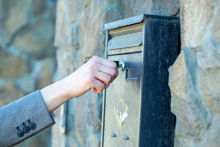 metal post: Female hand opens metal post box for correspondance with key on mural background