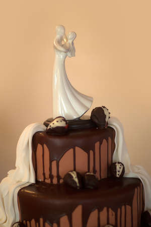 topper: Wedding cake with bride and groom porcelain figurine topper on beige background Stock Photo