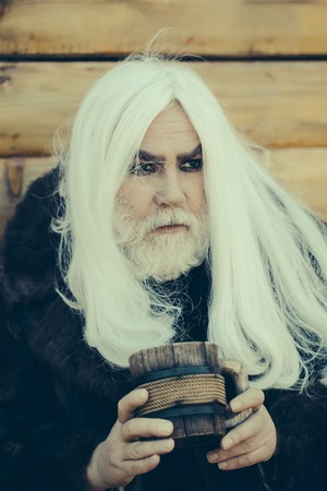Druid old man with long grey hair and beard on serious face with wooden mug in hands outdoor on wood background 写真素材