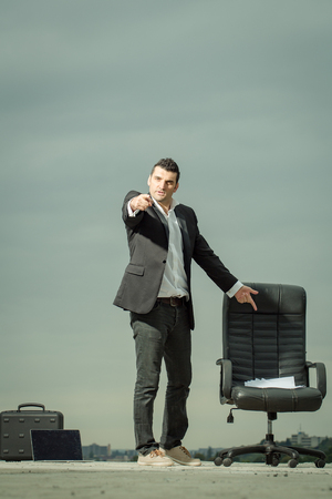 arm chair: handsome tired male businessman in black formal jacket and white shirt with laptop and paper near leather arm chair outdoor with briefcase on cloudy sky background