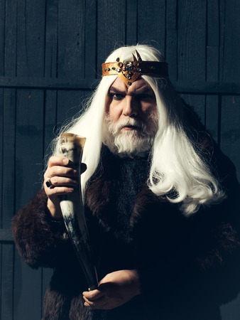 old druid bearded man with long beard on serious face and hair in fur coat and crown with gem stones jewellery on wooden background holding animal antler or horn 写真素材 - 113575459