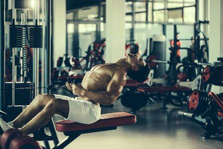 nackte brust: Gut aussehender junger Mann mit sexy muskulösen Körper nass und nackte Brust Training mit schweren Trainingsgeräten im Fitness-Studio