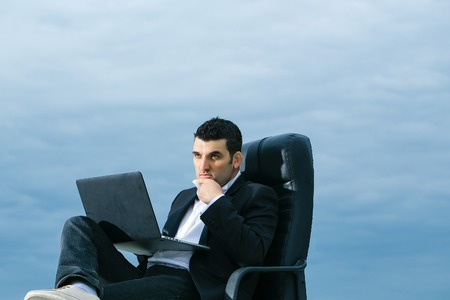 arm chair: handsome male businessman with courageous face in black formal jacket and white shirt working on laptop sitting on leather office arm chair outdoor on cloudy sky background