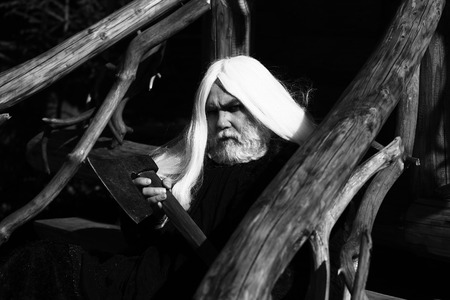 house coat: Old man druid with long silver hair and beard in fur coat holding big sharp axe on wooden house background sunny day outdoor, black and white