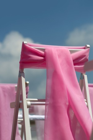 wedding chairs: Pink bows ribbon decoration on white wedding chairs on blue sky background