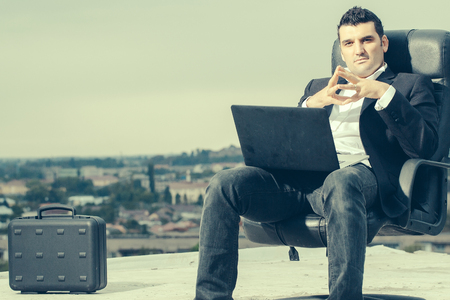 arm chair: handsome male businessman with courageous face in black formal jacket and white shirt working on laptop sitting on leather office arm chair with briefcase outdoor on cloudy sky background Stock Photo