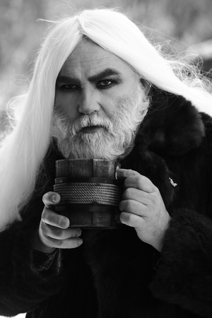 druid: Druid old man with long silver hair and beard in fur coat with wooden mug in hands black and white on grey background