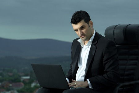 arm chair: handsome male businessman with courageous face in black formal jacket and white shirt working on laptop sitting on leather office arm chair outdoor on city background