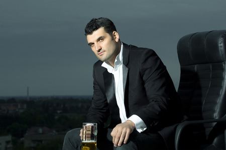 arm chair: handsome male businessman with courageous face in black formal jacket and white shirt holding beer glass sitting on leather office arm chair outdoor on city background