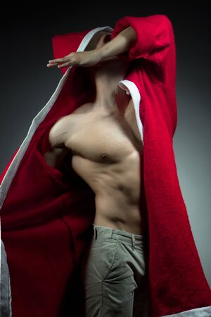 man power: sexual young new year man with muscular body in red christmas santa coat posing on studio background Stock Photo
