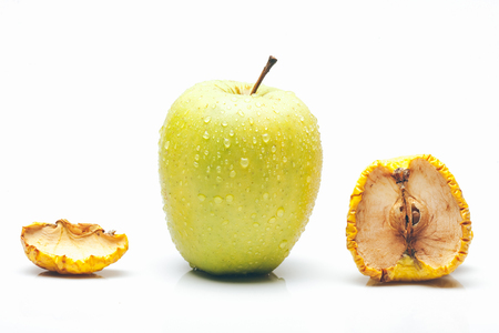 aging concept: fresh green apple with water drops compared with dried and wrinkled pieces with seeds isolated on white background, time or aging concept