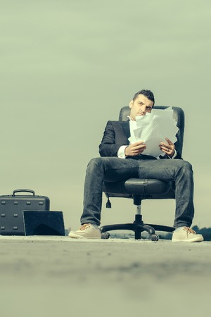 arm chair: handsome male businessman in black formal jacket and white shirt with laptop and paper on leather arm chair outdoor with briefcase on cloudy sky background Stock Photo