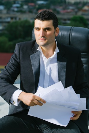 arm chair: handsome serious male businessman in black formal jacket and white shirt with paper on leather arm chair outdoor on city background
