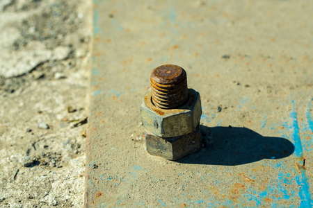 screwed: Rusty screw metal nut screwed with corroded bolts on steel beam on grungy background