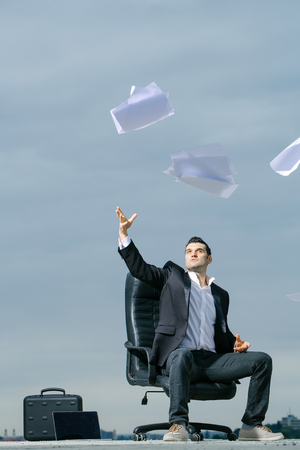 arm chair: handsome male businessman in black formal jacket and white shirt with laptop and briefcase throwing paper on leather arm chair outdoor on cloudy sky background
