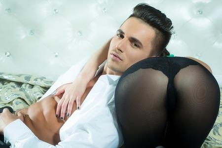 nackte brust: gut aussehender junger Mann mit sexy muskulösen Körper und nackte Brust mit Torso in offenen weißen Hemd in der Nähe von weiblichen Gesäß in schwarzen Strümpfen