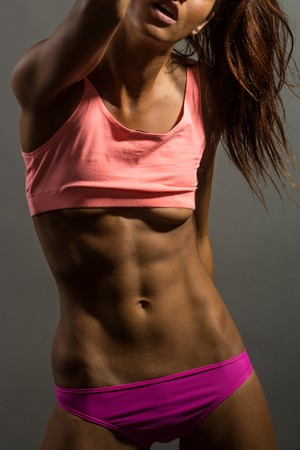 six packs: young sporty girl with pretty face and slim sexy body and bare belly with six packs in pink sportswear in studio on grey background Stock Photo
