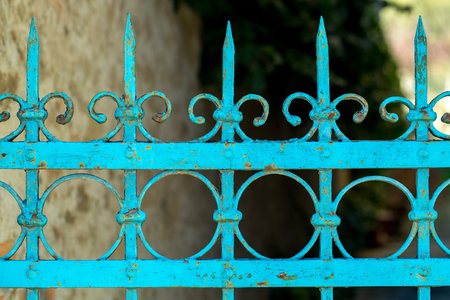 metallized: Old fence rusty forged metallized with peeled blue paint on sunny day on blurred background