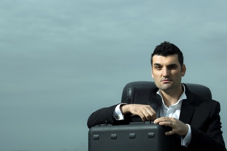 brief case: handsome male businessman with serious face in black formal jacket and white shirt with brief case on leather office arm chair outdoor on cloudy sky background, copy space