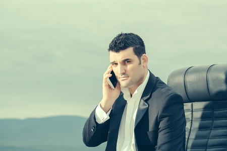 arm chair: handsome male businessman with serious face in black formal jacket and white shirt speaking on mobile phone sitting on leather office arm chair outdoor on cloudy sky background Stock Photo