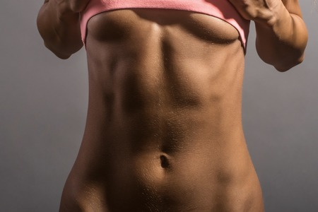 six packs: young sporty girl with slim sexy body and bare belly with six packs in pink sportswear in studio on grey background