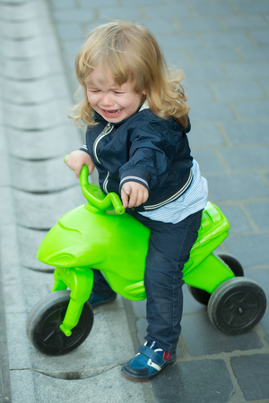 cries: Little boy with blond long hair cries and sits on bicycle outdoor on grey street pavement Stock Photo