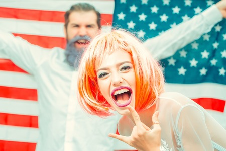 Happy young patriotic Americans bright make up and hair celebrating Independence Day on 4th of July. American flag on the background, cute heterosexual couple, girl with the bright orange hair Stock Photo
