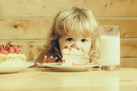 strawberry blonde: cute little boy child with long blonde hair eating tasty creamy pie or cake with red strawberry fruit and glass of yogurt