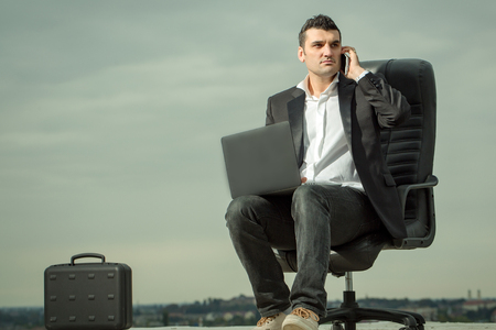 arm chair: handsome male businessman in black formal jacket and white shirt working on laptop sitting on leather office arm chair with briefcase and mobile phone outdoor on cloudy sky background
