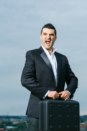 brief case: handsome male businessman with shouting face in black formal jacket and white shirt with brief case on leather office arm chair outdoor on cloudy sky background