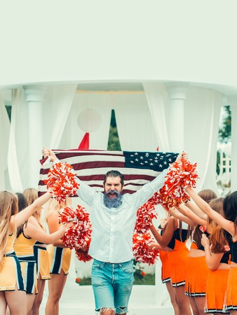 bobble: young patriotic happy bearded man with long blue beard holding american flag outdoor celebrating independence day usa with cheerleader team dancing with pompons Stock Photo
