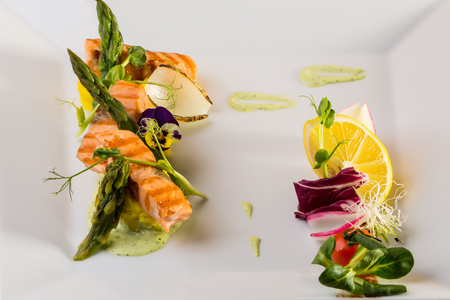 garnished: Grilled salmon steaks garnished with sauce lemon flower asparagus and vegetables on white background
